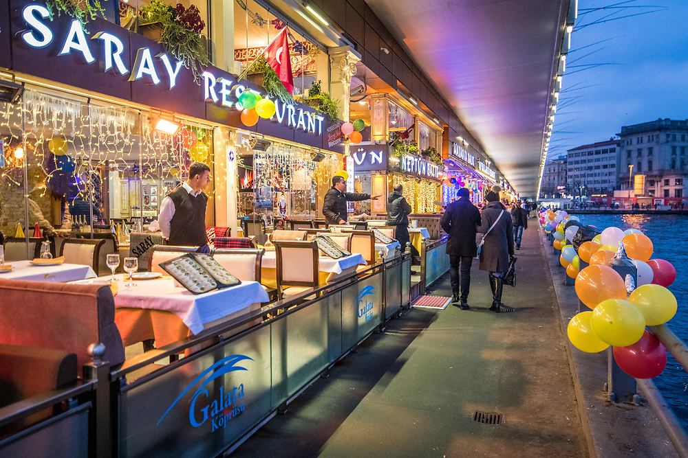 Servers patiently await customers at illuminated waterfront resturant located on the Golden Horn in Istanbul, Turkey