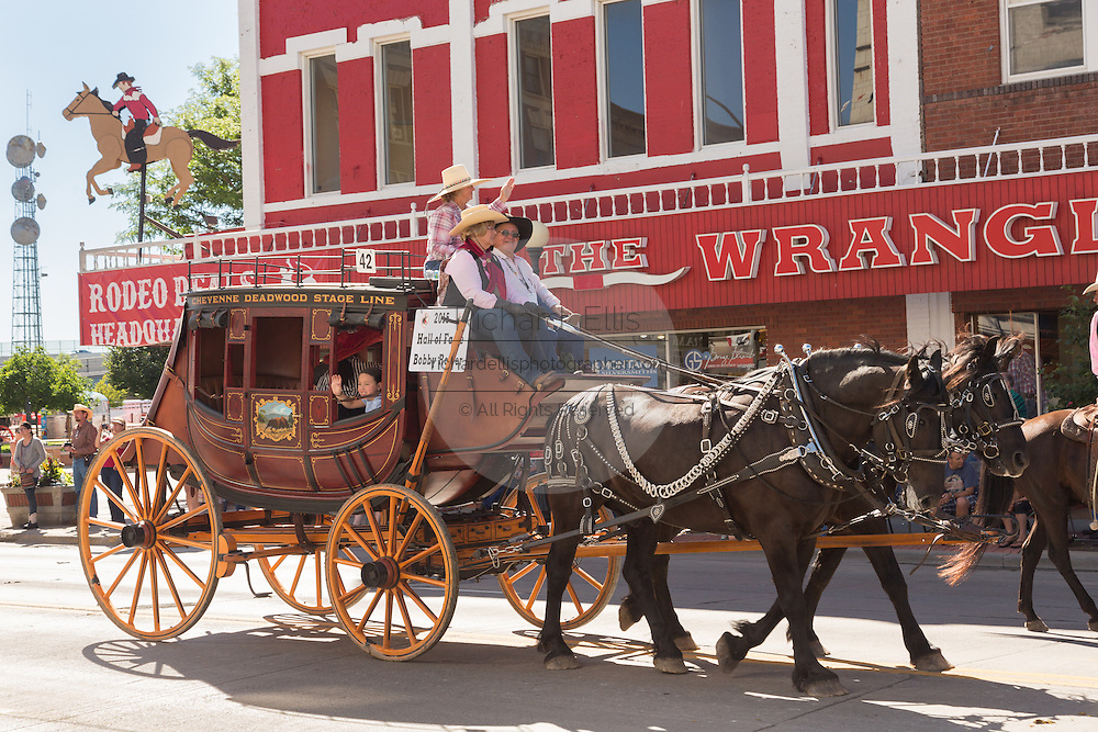 A stagecoach wagon pasts the Wrangler western wear store during the Cheyenne Frontier Days parade through the state capital July 23, 2015 in Cheyenne, Wyoming. Frontier Days celebrates the cowboy traditions of the west with a rodeo, parade and fair.