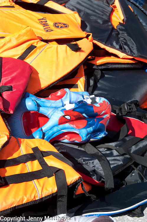 Greece. Lesvos. Patra. Discarded lifevests, including a child's spiderman one, from newly arrived refugees.