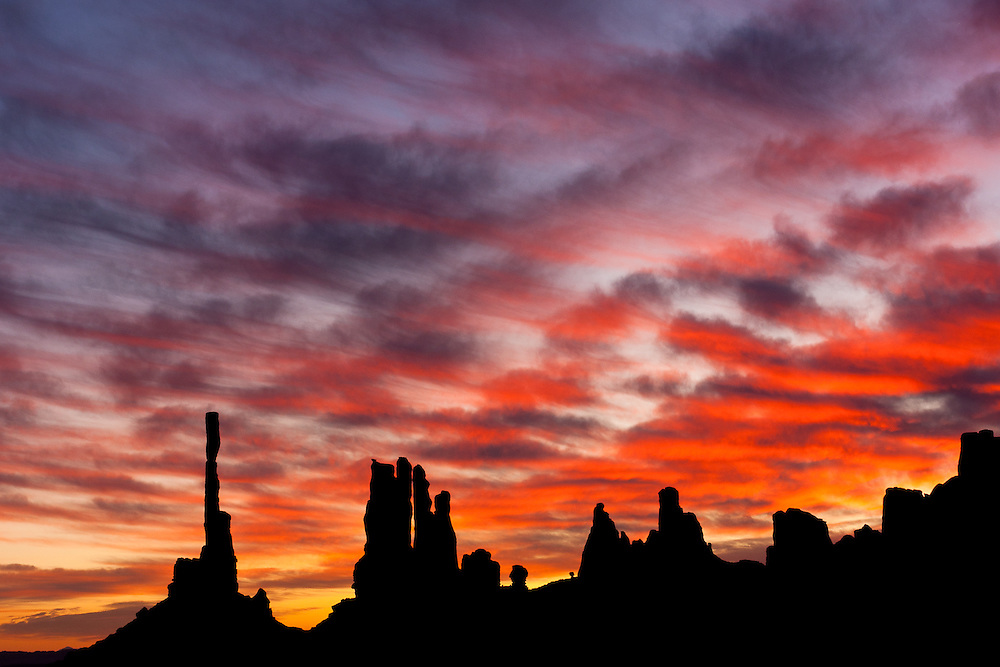As the sun rises, the clouds behind the formations of Totem Pole and Yey Bi Chei light up with crimson and reddish colors.