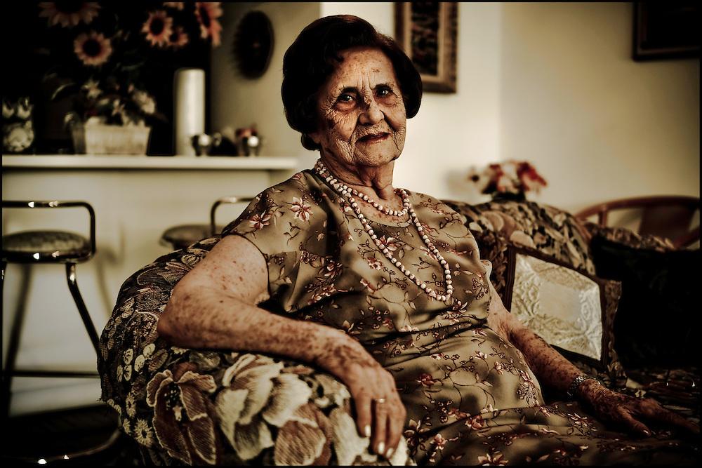 PORTRAITS OF SURVIVORS AND IMMIGRANTS <br /> Sobreviviente del Holocausto / Holocaust Survivor<br /> <br /> Sra. Alegre Calder&oacute;n de Sa&iacute;as.<br /> <br /> Naci&oacute; en Sal&oacute;nica, Grecia, el 4 de febrero de 1923. En 1943 la zona  de la ciudad donde su familia viv&iacute;a fue transformada en un gueto, donde tuvieron que quedarse - a excepci&oacute;n de una hermana casada y mudada a Siria - para despu&eacute;s ser llevados a Auschwitz. Fue conducida a Bergen-Belsen, y tras la liberaci&oacute;n, de nuevo al sitio natal. En Sal&oacute;nica se reencontr&oacute; con un viejo conocido con el que se cas&oacute;. Fueron primero a Estados Unidos y se instalaron en Venezuela en 1956.<br /> <br /> Photography by Aaron Sosa<br /> Caracas - Venezuela 2010<br /> (Copyright &copy; Aaron Sosa)
