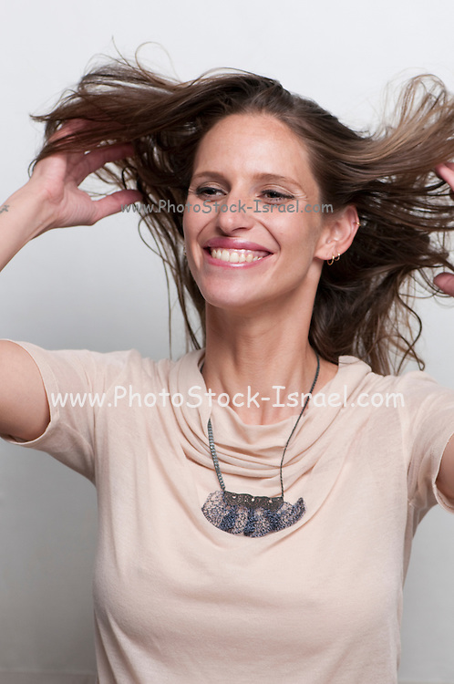A laughing, hip and trendy young woman on white background Model release available