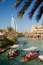 Abra water taxis carrying guests on canals at Madinat jumeirah hotels in Dubai in United Arab Emirates