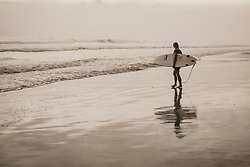 Surfer heading in to surf after sunset, Santa Teresa, Costa Rica