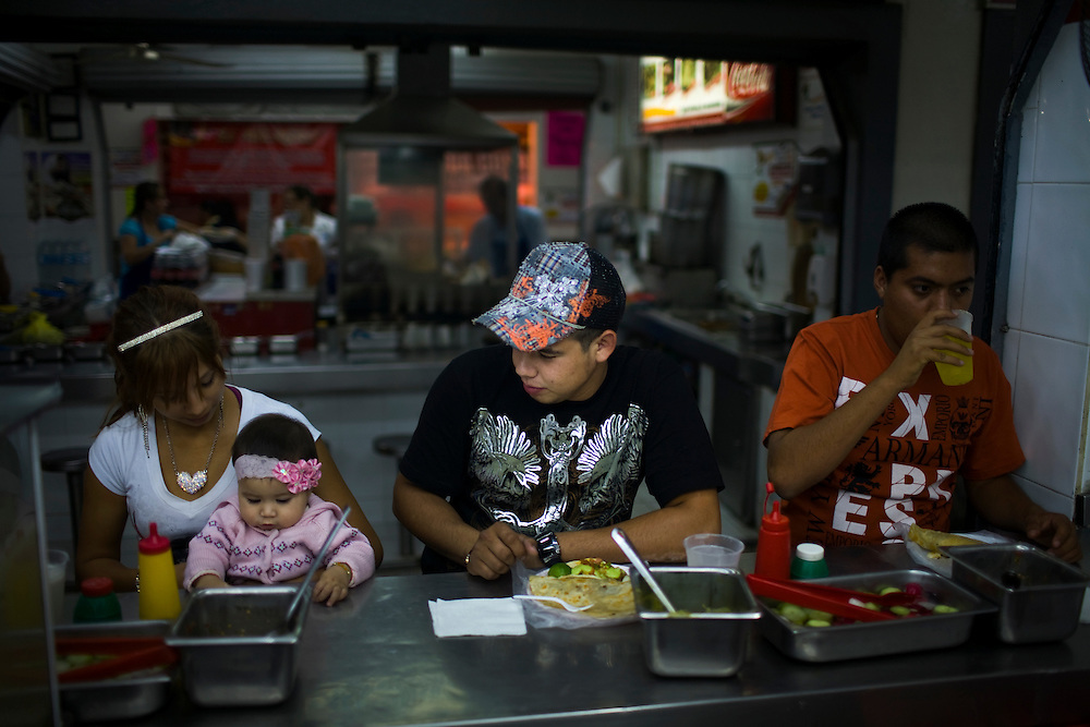 A young man dressed in the a flashy shirt and hat, whose style is representative of the Mexico's Narco Culture, eats dinner at a taco stand in Culiacan, Mexico.