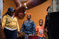 """Love and Live Again Ministries pastor Lafayette Dorsey, Sr. has weekly bible study classes in his living room, that Maxwell """"Bunchie"""" Young, 10, and his dad are regulars at. Following an hour-long lesson, Bunchie, center, and the others in attendance stand and hold hands in prayer. Faith plays almost as large a part in Bunchie's life as football does."""