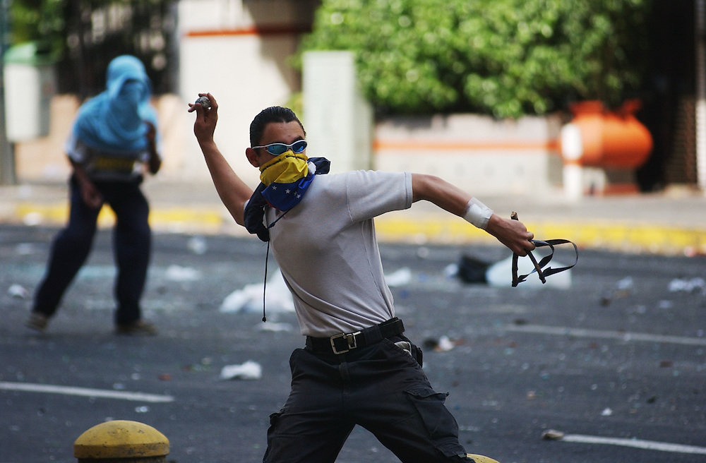 An anti-government protestors throws stones at National Guardsmen  as riots continued in Caracas between the two groups. The country is awaiting a preliminary decision on the validity of signatures seeking a recall referendum.  It is expected that hundreds of thousands of signatures will have to go to a review process that the opposition will refuse to submit to.