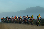 The lead bunch rides into the sunrise during stage 5 of the 2014 Absa Cape Epic Mountain Bike stage race held from The Oak Estate in Greyton to Oak Valley Wine Estate in Elgin, South Africa on the 28 March 2014<br /> <br /> Photo by Greg Beadle/Cape Epic/SPORTZPICS