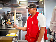 "26 JUNE 2020 - DES MOINES, IOWA: ENRIQUE HERNANDEZ makes deep fried foot long corn dogs in the American Grill trailer at Fair Food Friday in Des Moines. The 2020 Iowa State Fair, like many state fairs in the Midwest, has been cancelled this year because of the COVID-19 (Coronavirus) pandemic. The cancellation of the fair left many small vendors stranded with no income. Some of the fair food vendors in Iowa started ""Fair Food Fridays"" on a property a few miles south of the State Fairgrounds. People drive up and don't leave their cars while vendors bring them the usual midway fare; corndogs, fried tenderloin sandwiches, turkey legs, deep fried Oreos, lemonaide and smoothies. Fair Food Friday has been very successful. The vendors serve 450-500 people per Friday and during the lunch rush people wait in line in their cars 30 - 45 minutes to place an order.      PHOTO BY JACK KURTZ"