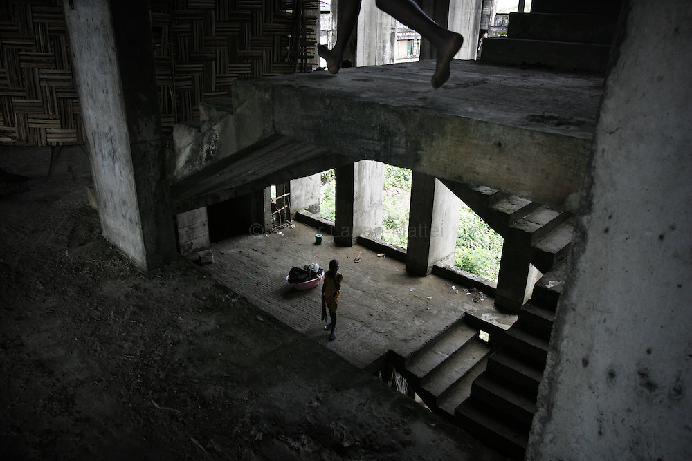 """Photo taken 19 September 2005 of an interior view of the former uncompleted Ministry of National Defense building in Congo Town on the outskirts of Monrovia. The """"Pentagon"""", named this way by its occupants, shelters 394 families totalling approximately 3,000 people who were booted out in May 2005 of the Barclay Training Center, which had been their home for the last two decades. Former soldiers, who fought for former Liberian presidents Samuel Doe and Charles Taylor, live in this building with no water or electricity, overcoming past differences. The construction of the building started in 1984 under Doe's leadership, and the war interrupted the its completion and later served as a base for Taylor's men."""