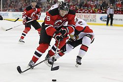 Apr 7; Newark, NJ, USA; New Jersey Devils defenseman Adam Larsson (5) skates with the puck while being defended by Ottawa Senators left wing Zack Smith (15) during the first period at the Prudential Center.
