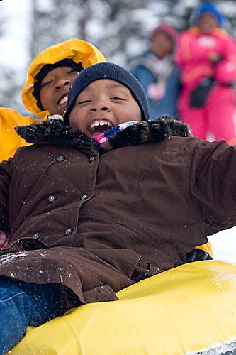 Young kids riding snowtube at Kirkwood ski resort near Lake Tahoe, CA.
