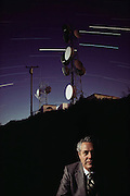 Jack Arnold - VP of Harris Corporation with Microwave relay telecommunication equipment on top of a mountain, outside Vacaville, California. Equipment was built with Harris components. Double exposure of Harris in his office with the long night exposure of the equipment on the mountaintop with star trails (due to the rotation of the Earth). MODEL RELEASED