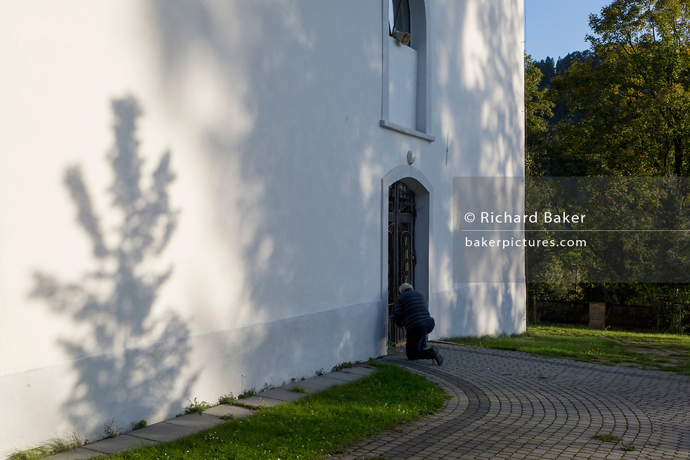A worshipper kneels and prays during Mass outside the Greek-Catholic Jana Chrzciciela church, on 21st September 2019, in Jaworki, near Szczawnica, Malopolska, Poland.