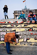 March 13, 1990. Berlin, Federal Republic of Germany. In front of Brandenburg Gate, Berliners and tourists alike help to reduce the Berlin Wall to rubble. (Photo Heimo Aga)