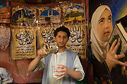 Boy at coffee stall in old city of Sanaa. Stall walls decorated with pictures of Mecca and people at prayer.