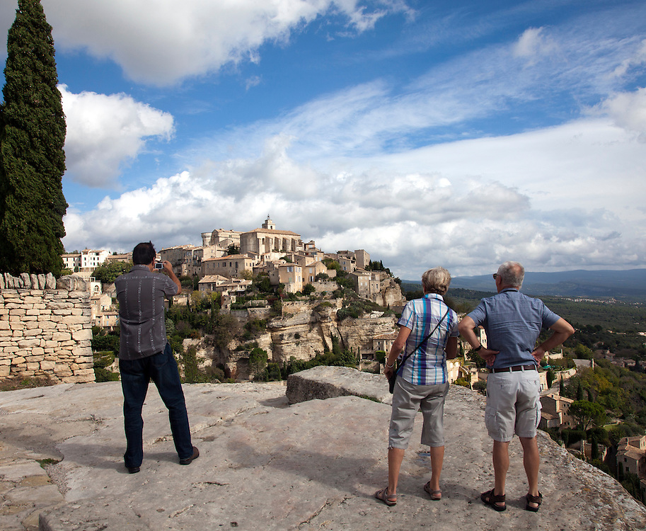 Tourists photographing the hilltop village of Gordes, Luberon area of Provence, France.