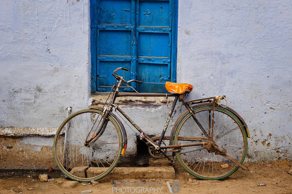 a bicycle laying below a blue window