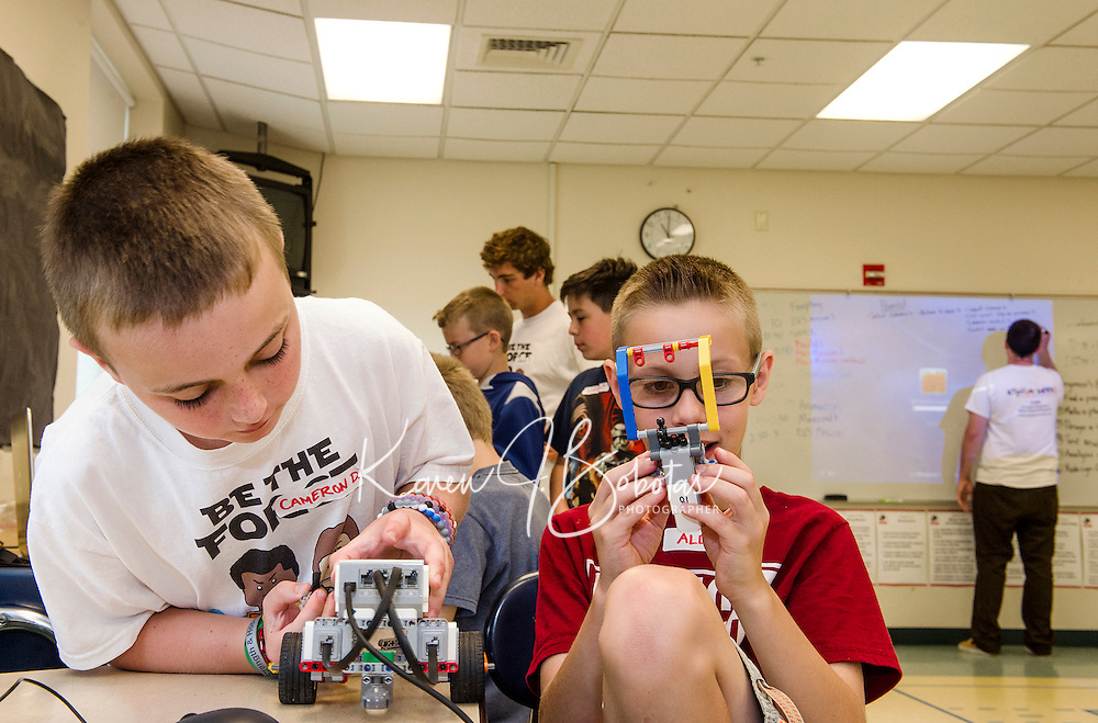 """Cameron and Alden add a lift to their Lego robotic droid during """"Let Go Your Mind"""" summer camp through Gilford Parks and Recreation at the Gilford Middle School on Wednesday.  (Karen Bobotas/for the Laconia Daily Sun)"""