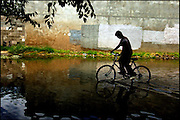 .After only a light afternoon rain, 13-year-old Julian Corona rides his bike through a flooded section of Flora Vista Dr SW, just east of property belonging to his grandfather Daniel Jojola on Friday, August 12, 2005.