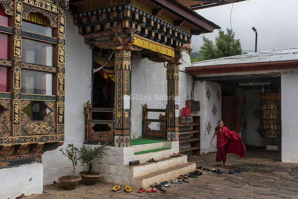 For a story by Steven Lee Myers, Bhutan<br /> Lobesa, Bhutan, August 2nd, 2017<br /> A young monk entering Chimi Lhakhang temple for the morning prayers. The temple is built on the site where it is said that Lama Drukpa Kunley  popularly known as the &ldquo;Divine Madman&quot;  subdued a demon with his &ldquo;magic thunderbolt of wisdom&rdquo;. <br /> The Bhutanese tradition of using phallic symbols as a protection from evil spirits is linked to Lama Kunley, but find its origins in the Bon religion that predated Buddhism in Bhutan.<br /> Gilles Sabri&eacute; pour The New York Times