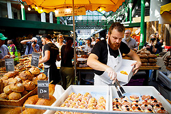 © Licensed to London News Pictures. 14/06/2017. London, UK. Shop owners start trading as Borough Market in London reopens on 14 June 2017, following a terror attack that killed 8 people over a week ago. Photo credit: Tolga Akmen/LNP