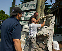 Alfonso Danzuso, Tony Puzzo and Jason Rook blend panel masonry pieces together as they construct a waterfall at Lakeshore Landing with Diversified Dock and Marine / Scuba Supply / Outdoor Living on Friday afternoon.   (Karen Bobotas/for the Laconia Daily Sun)