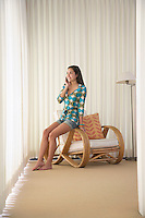 Teenage girl (16-18) sitting on armchair talking on mobile phone