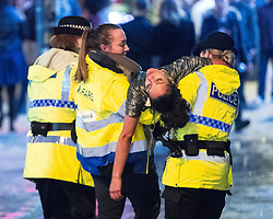 © Licensed to London News Pictures . 01/01/2018. Manchester, UK. Police and a welfare support worker lift a woman off the ground and carry her away from the Printworks . Revellers celebrate the start of the New Year in Manchester City Centre . Photo credit: Joel Goodman/LNP