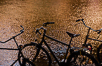 Amsterdam, Holland. Silhouetted bicycles along a canal.