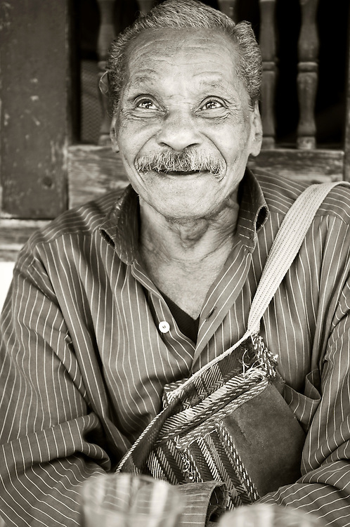 A man in his 80s, sitting and smiling outside a cafe in Cairo, Egypt