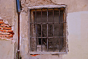 An old window with iron bars and exposed brick in Valladolid, Spain.