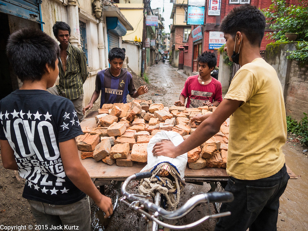 06 AUGUST 2015 - KATHMANDU, NEPAL: Laborers recycle bricks from a house in Kathmandu that was destroyed in the Nepal Earthquake. The Nepal Earthquake on April 25, 2015, (also known as the Gorkha earthquake) killed more than 9,000 people and injured more than 23,000. It had a magnitude of 7.8. The epicenter was east of the district of Lamjung, and its hypocenter was at a depth of approximately 15km (9.3mi). It was the worst natural disaster to strike Nepal since the 1934 Nepal–Bihar earthquake. The earthquake triggered an avalanche on Mount Everest, killing at least 19. The earthquake also set off an avalanche in the Langtang valley, where 250 people were reported missing. Hundreds of thousands of people were made homeless with entire villages flattened across many districts of the country. Centuries-old buildings were destroyed at UNESCO World Heritage sites in the Kathmandu Valley, including some at the Kathmandu Durbar Square, the Patan Durbar Squar, the Bhaktapur Durbar Square, the Changu Narayan Temple and the Swayambhunath Stupa. Geophysicists and other experts had warned for decades that Nepal was vulnerable to a deadly earthquake, particularly because of its geology, urbanization, and architecture.      PHOTO BY JACK KURTZ