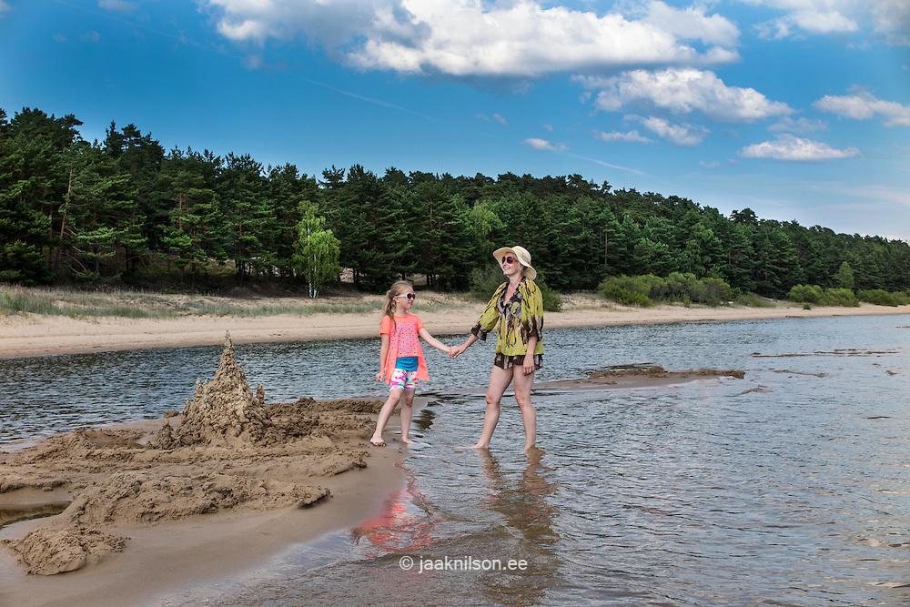 Daughter and mother standing on Kauksi beach, hand in hand. Lake Peipsi in Estonia.
