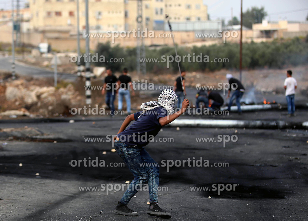 19.10.2015, Ramallah, PSE, Nahostkonflikt zwischen Israel und Pal&auml;stina, im Bild Zusammenst&ouml;sse zwischen Pal&auml;stinensischen Demonstranten und Israelischen Sicherheitskr&auml;fte // A masked Palestinian protester uses a sling shot to throw stones during clashes with Israeli borderguards next to the Jewish settlement of Beit El. More than two weeks of unrest have raised warnings of the risk of a full-scale Palestinian uprising, while some Israeli politicians have urged residents to arm themselves to fend off the threat of stabbings and gun assaults, Palestine on 2015/10/19. EXPA Pictures &copy; 2015, PhotoCredit: EXPA/ APAimages/ Shadi Hatem<br /> <br /> *****ATTENTION - for AUT, GER, SUI, ITA, POL, CRO, SRB only*****