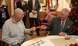 The Prince of Wales pulls a Christmas cracker with Andrew Kemp during a visit to the Sue Ryder Leckhampton Court Hospice near to Cheltenham in Gloucestershire, which he visits regularly and is celebrating 30 years of royal patronage.