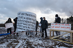 © London News Pictures. Calais, France. 07/03/16. Iranian men currently on hunger strike stand with signs and placards as police enter the 'Jungle' camp. French authorities are evicting and demolishing the southern half of the Calais 'Jungle' camp, which charities estimate to contain 3,500 people. . Photo credit: Rob Pinney/LNP