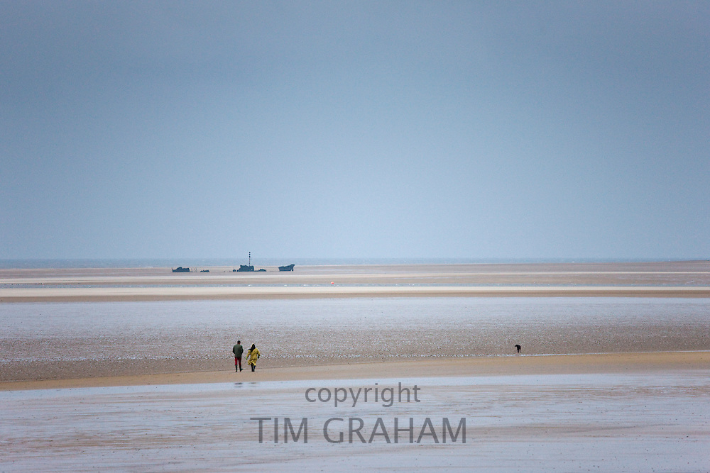 Walkers stroll along the shoreline walking their dog in winter at Holkham beach, North Norfolk, UK