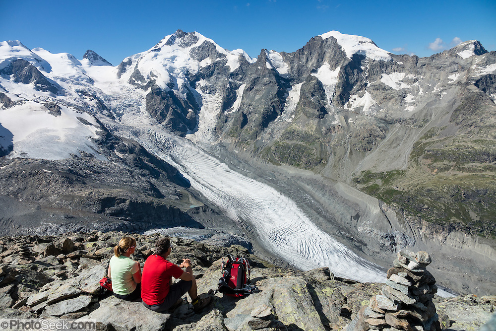 """Above Morteratsch Glacier rise Piz Bernina (4049 m) and Piz Morteratsch in Graubünden (or Grisons / Grigioni / Grischun) canton of Switzerland, the Alps, Europe. From Diavolezza cable car station, admire tremendous views of the icy Bernina Range. If not afraid of heights at Diavolezza, don't miss the magnificent hike to rocky Munt Pers (gaining 265 meters over just 4 km round trip). The Swiss valley of Engadine translates as the """"garden of the En (or Inn) River"""" (Engadin in German, Engiadina in Romansh, Engadina in Italian) and is part of the Danube basin."""