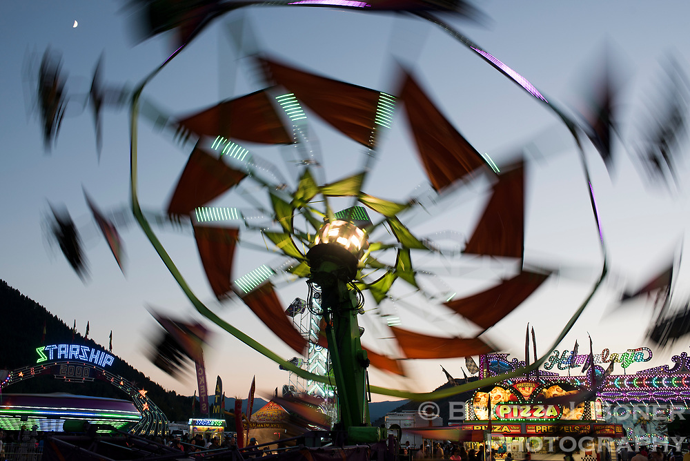 Carnival rides spin into the night at dusk Saturday at the Teton County Fair.