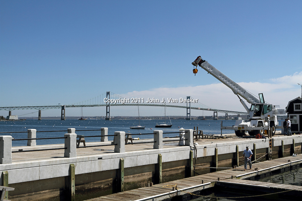 Repair work being conducted on the Jamestown waterfront pier. Ferries run between Jamestown and Newport, Rhode Island across the Narragansett Bay. The Claiborne Pell Bridge is in the background. Jamestown, Rhode Island, USA.