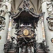 Front view of the ornately carved wooden pulpit at the Cathedral of St. Michael and St. Gudula (in French, Co-Cathédrale collégiale des Ss-Michel et Gudule). A church was founded on this site in the 11th century but the current building dates to the 13th to 15th centuries. The Roman Catholic cathedral is the venue for many state functions such as coronations, royal weddings, and state funerals. It has two patron saints, St Michael and St Gudula, both of whom are also the patron saints of Brussels.