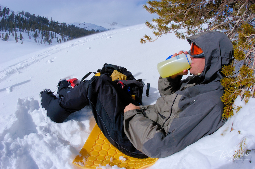 Backcountry skier having a drink and enjoying the view along Lee Vining Creek, Inyo National Forest, Sierra Nevada Mountains, California