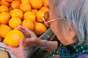 Elderly Asian woman checking an orange