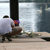 A mourner places a note at a small makeshift memorial at Lake Eola Park flagpole for the victims of the Pulse nightclub where many victims were killed in the deadliest shooting in modern U.S. History on Tuesday,   June 14, 2016, in Orlando, Fla. (Alex Menendez via AP)
