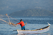 A fisherman casts a net into Lake Catemaco as a heron bird rests on the bow of his boat in Catemaco, Veracruz, Mexico. The tropical freshwater lake at the center of the Sierra de Los Tuxtlas, is a popular tourist destination and known for free ranging monkeys, the rainforest backdrop and Mexican witches known as Brujos.