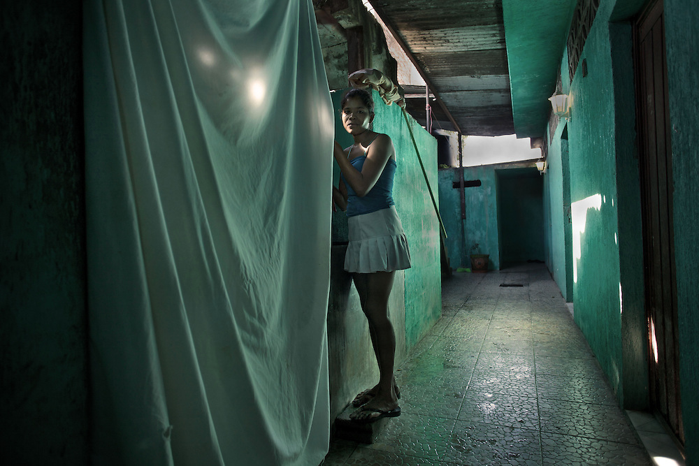 Cristina, 21 from Guatemala. Busy to wash clothes of the previous night inside the brothel. Huixtla,Chiapas. - Prostitution on Mexican Southern Border