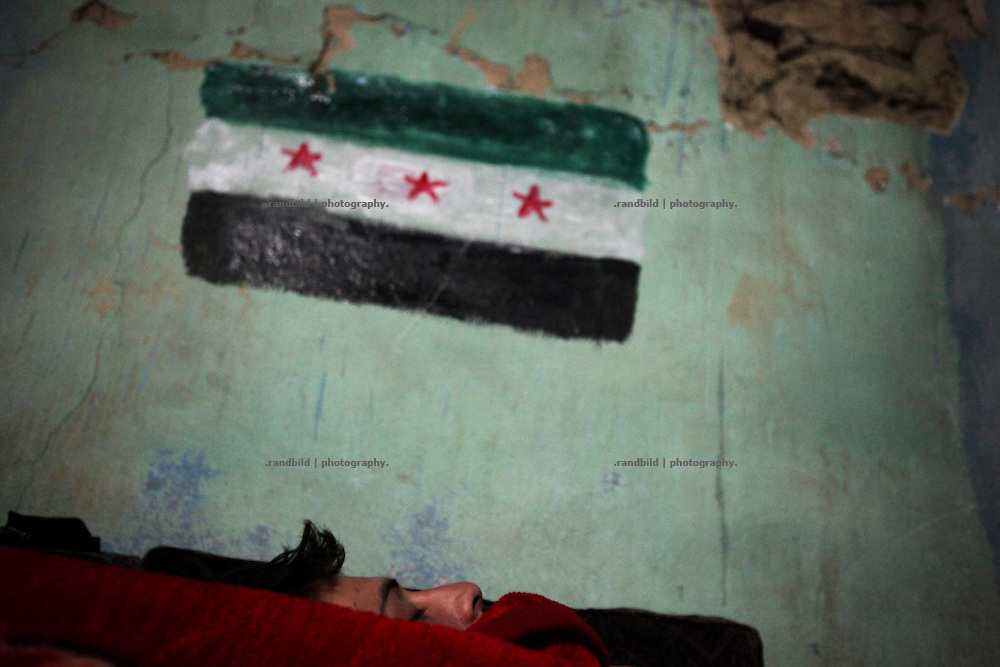 A member of the Free Syrian Army sleeps in a makeshift headquarters of the FSA in Al Janoudiyah, Province of Idlib, Syria. The revlolutionary flag is painted on the wall behind.