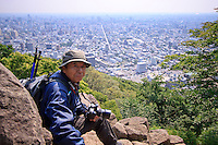 An elderly male hiker looks from the summit of Mt Maruyama out over Sapporo city, Hokkaido, Japan.