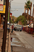 Businesses line a street in Nogales, Sonora, Mexico, along the border wall at Nogales, Arizona, USA.